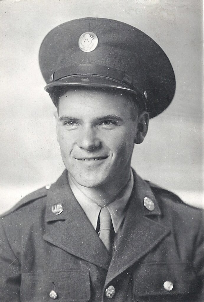 Black and white portrait, head and shoulders of a young man in a military uniform with a military hat that has a shiny button on the center of it. He is smiling.